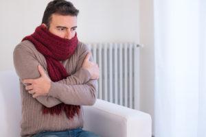 Un homme ayant froid lors d'une panne de chauffage en plein hiver